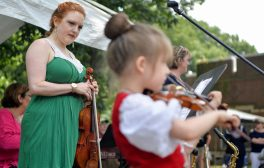 Rachel Barton Pine, left, of Chicago, watches her daughter Sylvia Pine, 5, play a song on the violin at the 101st Annual Scottish Home Picnic in North Riverside on Aug. 5. | Alexa Rogals/Staff Photographer