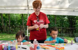 June Torrance, middle, of Palos Park, helps siblings Hannah, 4, and Levi Schuh, 5, with their craft project during the 101st Annual Scottish Home Picnic in North Riverside on Aug. 5. | Alexa Rogals/Staff Photographer