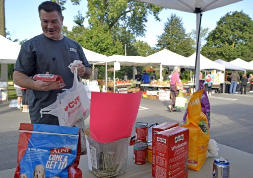 Ed Petrak, of Brookfield, donates dog food and treats on Sept. 2, for Hurricane Harvey victims during the Brookfield farmers market at Village Hall in Brookfield. | Alexa Rogals/Staff Photographer