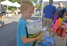 Henry Polanek, 8, of North Riverside, donates dog food on Sept. 2, for Hurricane Harvey victims during the Brookfield farmers market at Village Hall in Brookfield. | Alexa Rogals/Staff Photographer