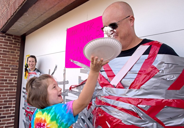 """In addition to being duct-taped to a wall outside the building, Central School Principal Peter Gatz get a face full of whipped-cream pie on Oct. 20, as the climax to a school-wide effort to raise funds for disaster relief in Florida, Texas, California and Puerto Rico. In addition to Gatz, students """"voted"""" (by donating change to a jar in her homeroom) to duct-tape fifth-grade teacher Laura McMahon to the wall. 