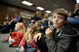 Children eat candy canes and watch as magic tricks are performed on Dec. 2, during the annual Holiday Walk and celebration throughout Brookfield. | ALEXA ROGALS/Staff Photographer
