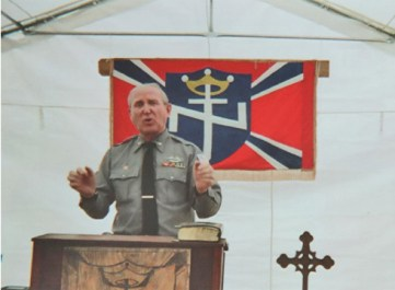A photo on Art Jones' campaign website shows him wearing something resembling a military uniform while speaking at the Aryan Nations 2014 World Congress in Converse, Louisiana. | Photo courtesy artjonesforcongressman.com