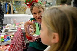 Michelle Nilles, left, shows Alyssa Katzin, 9, of Brookfield, the snowman she painted on her face inside the Prehop Cleaners during the Riverside's Chamber of Commerce 43rd Annual Holiday Stroll on Dec. 1. | Alexa Rogals/Staff Photographer