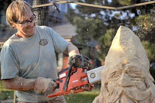 Bud Hainzinger, owner of Wooden Matter Carving Company, carves a Christmas gnome in front of Grossdale Station during the annual Holiday Walk and celebration throughout Brookfield on Dec. 2. | Alexa Rogals/Staff Photographer