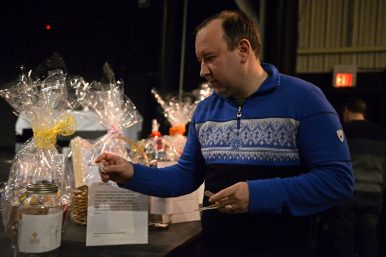Mark Bradford, of Riverside, puts a raffle ticket into one of the silent auction gifts on Jan. 28, during the Riverside Winter Hootenanny at Beyond Words Dance Center.   Alexa Rogals/Staff Photographer