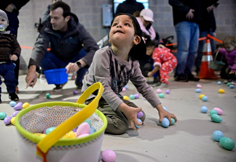 Children fill up their baskets with candy-filled eggs on March 24, inside the Riverside Public Works facility in Riverside Lawn for the village's annual Easter Egg Hunt. | Alexa Rogals/Staff photographer