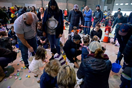Families help their children pick up candy-filled eggs on March 24, inside the Riverside Public Works facility in Riverside Lawn for the village's annual Easter Egg Hunt. | Alexa Rogals/Staff photographer