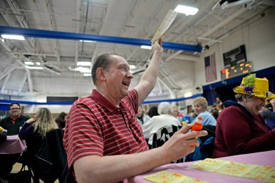 David Schroeder, of North Riverside, holds up his winning bingo cards in the air and wait for prizes on March 23, during Bunny Bingo at the Village Commons in North Riverside. | Alexa Rogals/Staff photographer