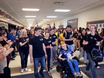 Ethan Tkalec got a police escort to school on April 27, was clapped into the building by an honor guard of students and zoomed his wheelchair around the RBHS cafeteria to the sounds of AC/DC. At the end of the school day (above), he was serenaded out of the building by the RBHS band with hallways lined with fellow students. | Bob Skolnik/Contributor