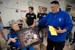 Lunch supervisor Rich Polfus, right, gives Ethan Tkalec a gift on April 27, during lunch inside the cafeteria at Riverside Brookfield High School. | Alexa Rogals/Staff Photographer