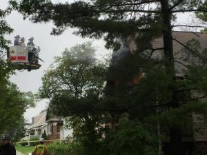 Firefighters assess the damage to 4312 Arthur Ave. after extinguishing the fire, which killed a woman who lived there. (Photo by Bob Uphues   Staff)