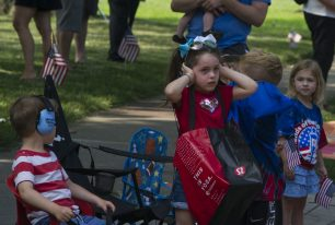 A child holds her hands over her ears to block out the sirens on July 4, during the Riverside 4th Of July Parade in Riverside. | Alexa Rogals/Staff Photographer