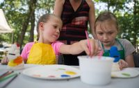 Sophia Ortega (left) and Jasari Ortega, both of Brookfield, paint piggy banks on Aug. 4 during the 102nd annual picnic at the Caledonia Senior Living and Memory Care in North Riverside. | Alexa Rogals/Staff Photographer