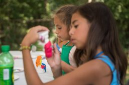 Children paint piggy paints at the kids tent on Aug. 4, during the 102nd annual picnic at the Caledonia Senior Living and Memory Care in North Riverside. | Alexa Rogals/Staff Photographer