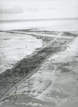 This photo shows Betio Island, looking west from its narrow eastern tip, shortly after the Battle of Tarawa. Red Beach is located near the top of the photo, on the right shore. The island's vegetation is almost stripped bare from the battle. U.S. military tents dot the tiny island.