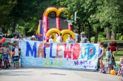 Kids and adults line up on Aug. 18 for the parade, which has kicked off the Maplewood Road Block Party for the past 30 years. Each year for the past six years, one family's name is drawn to display the Maplewood Road Award outside their home. | Alexa Rogals/Staff Photographer