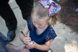 Isabell Hlavaty draws on a rock on Aug. 23, during a teddy bear picnic after the first day of kindergarten at Hollywood Elementary School in Brookfield. | Alexa Rogals/Staff Photographer
