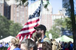 A participant wearing a military veteran hat, carrying an American Flag, walks on Sept. 22, during the American Foundation for Suicide Prevention Out of the Darkness Walk at Grant Park in Chicago. | Alexa Rogals/Staff Photographer