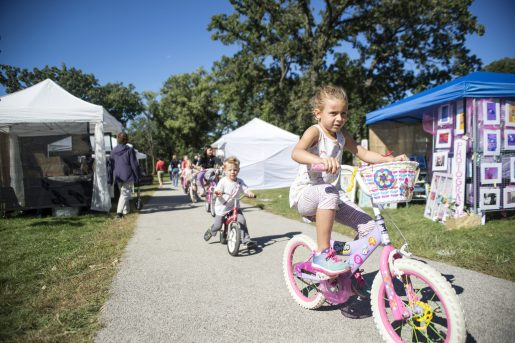 Children ride their bicycles down the sidewalk on Sept. 22, during the annual Fine Arts Festival at Kiwanis Park in Brookfield. | Alexa Rogals/Staff Photographer
