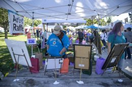 Attendees look through the artist raffle tent on Sept. 22, during the annual Fine Arts Festival at Kiwanis Park in Brookfield. | Alexa Rogals/Staff Photographer