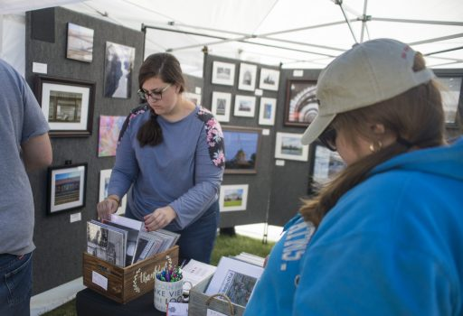 Chicago-based photographer Kelly Manteck digs through prints for a customer on Sept. 22, during the annual Fine Arts Festival at Kiwanis Park in Brookfield. | Alexa Rogals/Staff Photographer