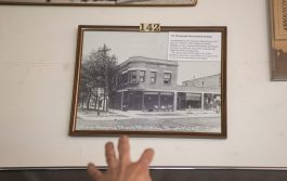 Kit Ketchmark points to a photo of the old bank building on Oct. 26, at the Grossdale Station Museum in Brookfield. | ALEXA ROGALS/Staff Photographer