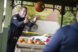 Brookfield Police Chief James Episcopo tosses a pumpkin to Ed Cote on the porch of the Grossdale Station before passing it out to one of hundreds of costumed visitors during the annual Monsters on Mainstreet trick-or-treating event on Oct. 27.   ALEXA ROGALS/Staff Photographer