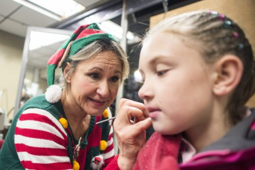 Michelle Nilles, left, paints a Christmas tree on Mia Marchetti's cheek on Dec. 7, at Prehop Cleaners during the 44th annual Chamber of Commerce Holiday Stroll in downtown Riverside. | Alexa Rogals/Staff Photographer