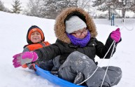 Children go sledding down the snowy hill on Feb. 10, at Commons Park behind the North Riverside Village Commons on Des Plaines Avenue. | Alexa Rogals/Staff Photographer