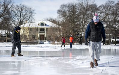 Members of the Big Chill Crew walk the around the liner for the ice rink at Big Ball Park to force out the air bubbles while water flowed into it from a hydrant on the morning of Jan. 26 in Riverside. | Alexa Rogals/Staff Photographer