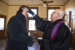 Dan Gregus (left) of Riverside, pauses as the Rev. Dale Jackson, pastor of Riverside Presbyterian Church, puts ashes on his forehead before boarding the Metra train to Chicago on Ash Wednesday, March 6, at the Riverside train station.   ALEXA ROGALS/Staff Photographer
