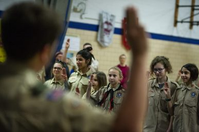 The new Scouts hold up their hands in the Scouts Salute on Feb. 27, during an induction ceremony for the Boy Scouts of America Troop 90GT at Brook Park Elementary School in La Grange Park. | ALEXA ROGALS/Staff Photographer