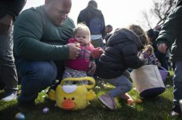 Toddlers get help from their parents scooping up as many plastic eggs as they can at Riverside Parks and Rec's annual Easter Egg Hunt at Big Ball Park on April 13. | Alexa Rogals/Staff Photographer