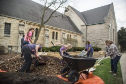 Church members help shovel up mulch to put in the garden beds. | Alexa Rogals/Staff Photographer