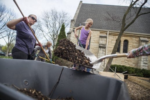 Church members help shovel mulch to put in the bottom of the garden beds before putting down the soil on April 22, at Ascension Lutheran Church on Nutall Road in Riverside. | Alexa Rogals/Staff Photographer