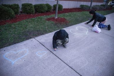 Community members use chalk to leave hearts and messages on the sidewalk on April 18, during a community prayer outside of the front entrance of George Washington Middle School. | ALEXA ROGALS/Staff Photographer