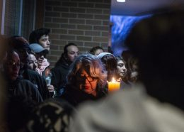 Community members gather and light candles on April 18, during a community prayer outside of the front entrance of George Washington Middle School. | ALEXA ROGALS/Staff Photographer