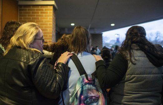 Parents comfort students on April 18, during a community prayer outside of the front entrance of George Washington Middle School. | ALEXA ROGALS/Staff Photographer
