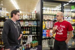 Riverside resident Paul Rau (right) and BuckleDown sales rep John Casiello talk about the brewery's special Riverside ale at a tasting event at Riverside Foods on April 26. (Alexa Rogals | Staff)
