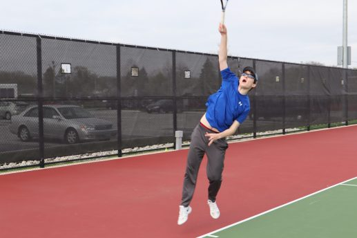 RBHS singles player William Dowling reaches high to hit a serve. (Submitted photo)