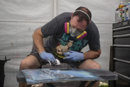Spray paint artist Nathan Bassett works on a piece in his booth on May 18, during the Riverside Arts Weekend, also known as RAW, at Guthrie Park in Riverside. | Alexa Rogals/Staff Photographer