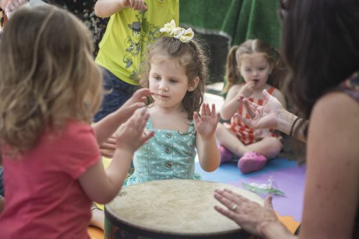 Children sing along and play the drums under the Early Childhood Music and Movement tent on Saturday, June 1, during the opening day of the farmers market at Brookfield Village Hall. | ALEXA ROGALS/Staff Photographer
