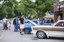 Attendees look over the different vehicles on Thursday, June 20, at the first night of the Cruise Nights event in downtown Riverside, Ill. | ALEXA ROGALS/Staff Photographer