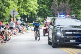 Riverside Police Officer Mike Panek waves as he pedals in the Riverside parade on July 4. (ALEXA ROGALS/Staff Photographer)