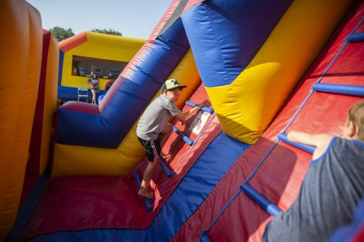 A pair of children race each other up one of the inflatable gyms on Saturday, July 27, during the North Riverside village block party in front of Village Commons on Des Plaines Avenue in North Riverside, Ill. (ALEXA ROGALS/Staff Photographer)