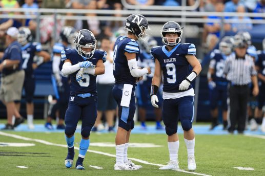 (Left to right) Nazareth players Alex Carrillo, J.J. McCarthy and Breven Reifsteck check a play call against Cardinal Ritter. The visiting Lions won 32-21 in LaGrange Park Aug. 31. (Photo by Ian McLeod)