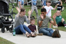 Alli and Tom Ferguson, of Clarendon Hills, perform the hand movements to the music Saturday, Sept. 21 as their son, Sam, 2, watches the performer at the Brookfield Fine Arts Festival.