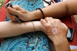 Izzi Markus with Apsire Too puts a henna design on Jean O'Laughlin, of Berwyn, on Saturday, Sept. 21 at the Brookfield Fine Arts Festival.