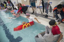 Teams line up their cardboard boats before the race on Oct. 9 during a physics class project in the pool at Riverside-Brookfield High School. (Alex Rogals/Staff Photographer)